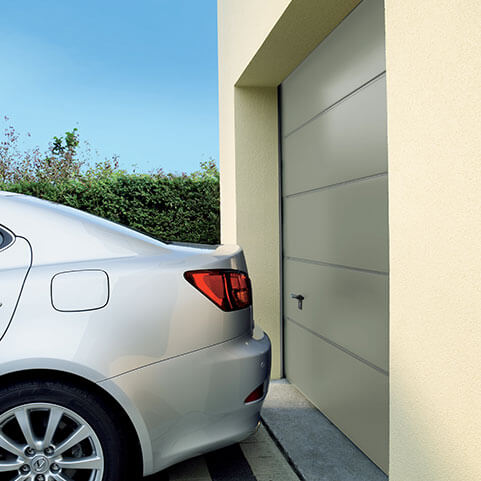 Car parked next to a garage door which has been made using high quality aluminium